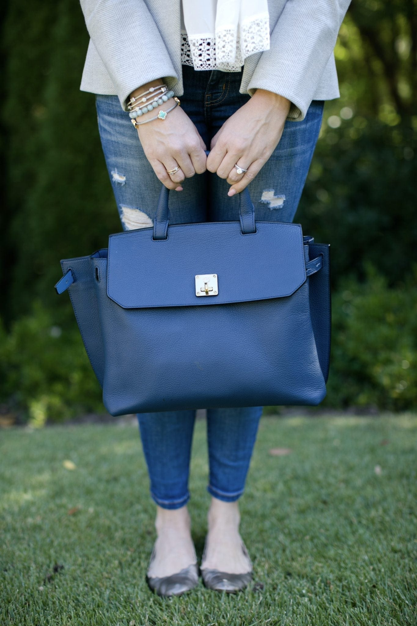 mcm blue backpack with veronica beard jacket with girl standing by green trees in chloe shoes