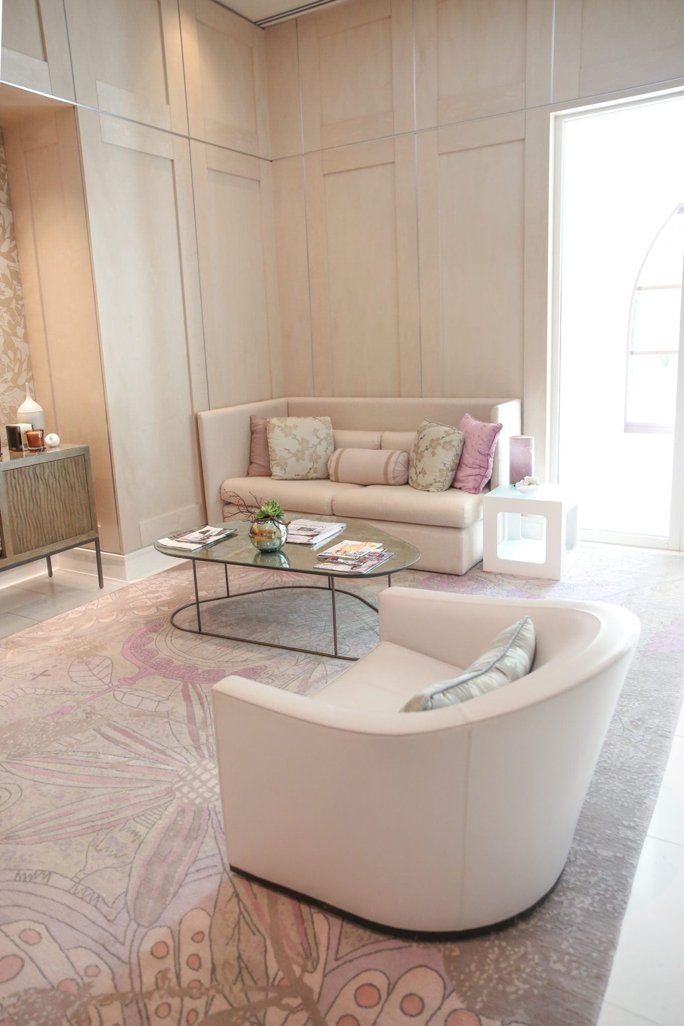 Four seasons spa with pink couch and antique mirror coffee table with pink throw pillows