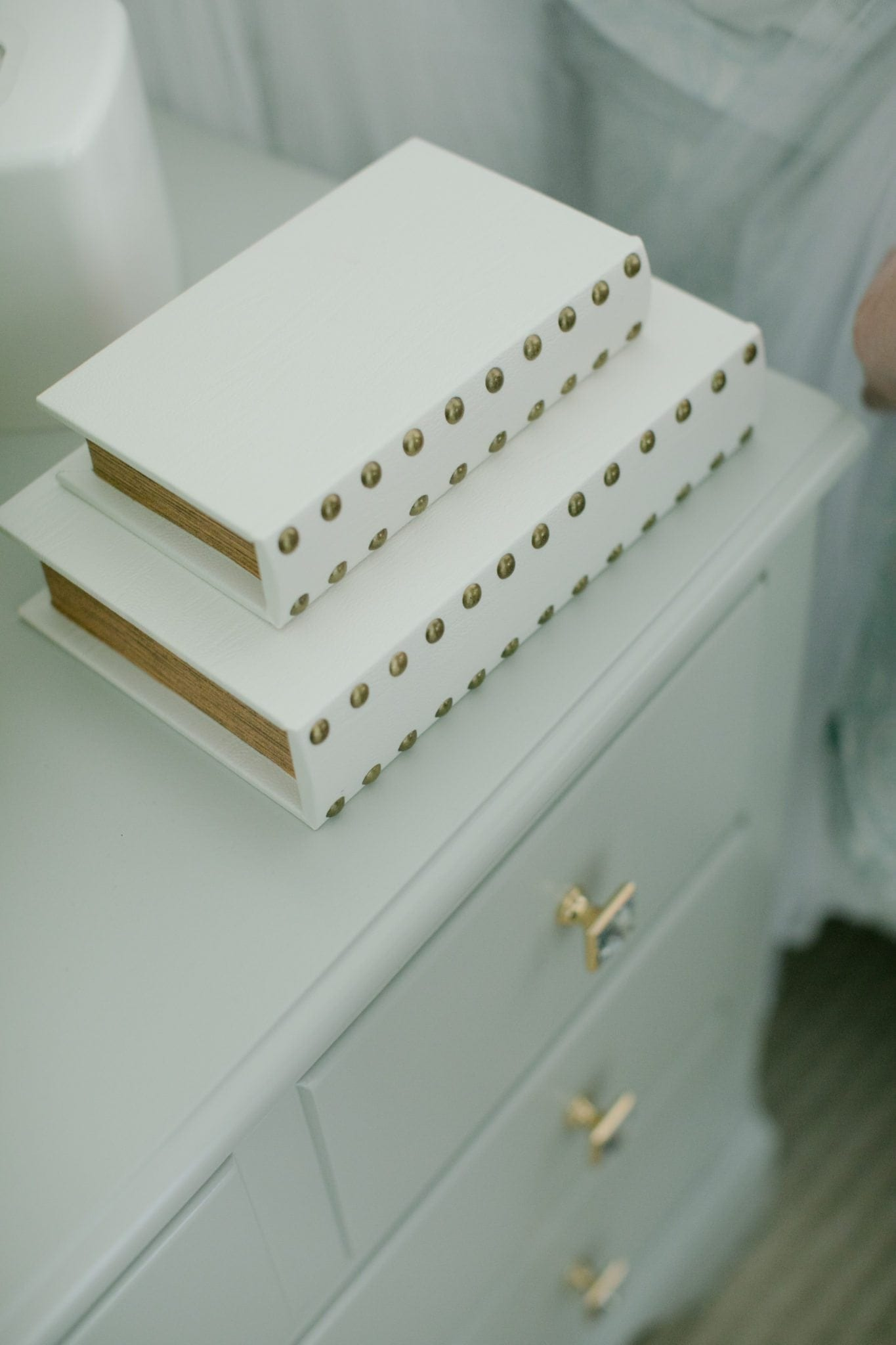 Decorative books with lids for hiding stuff on nightstand.