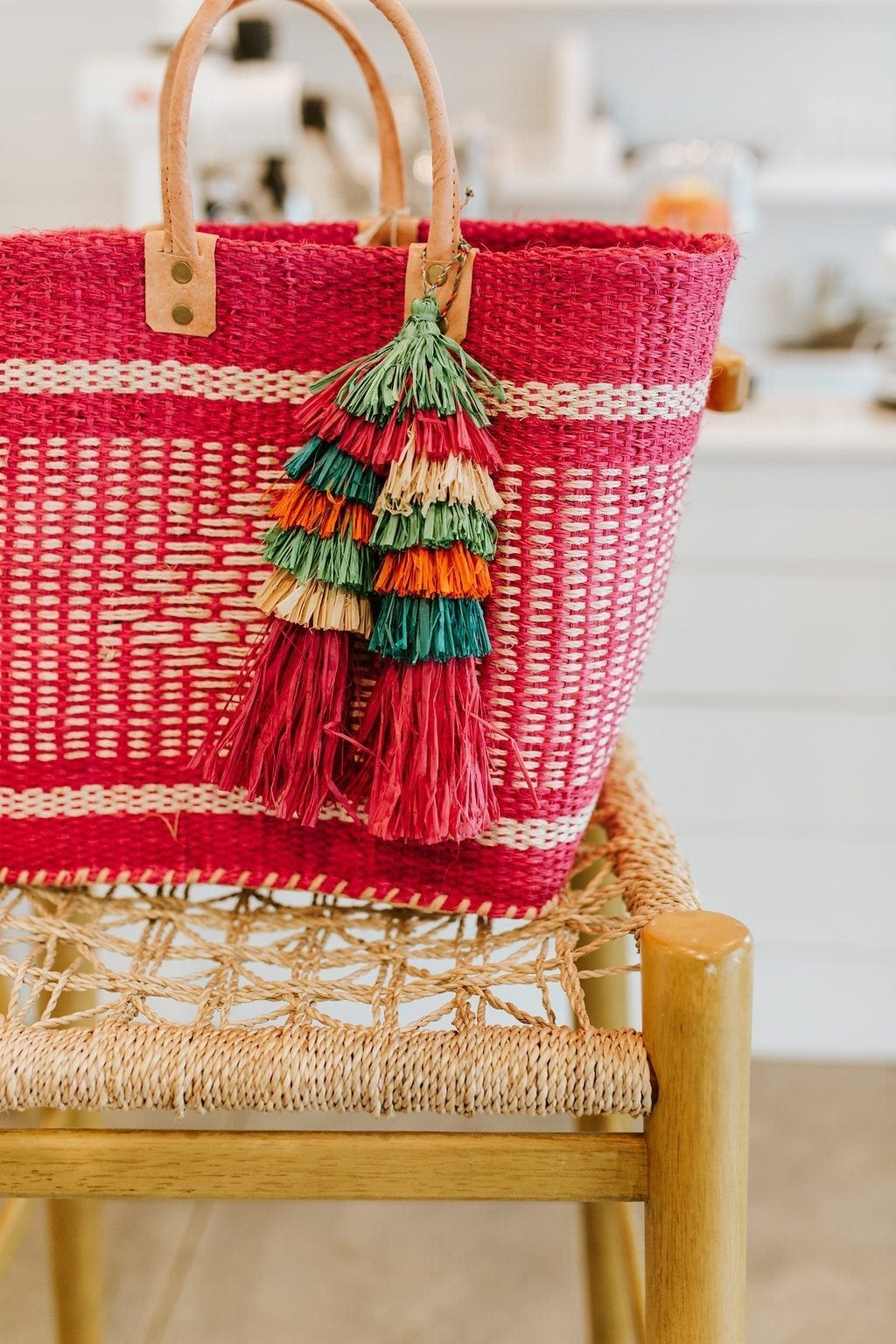 Pink straw tote bag with straw tassels. Multi color tassels hand from bright pink straw bag.