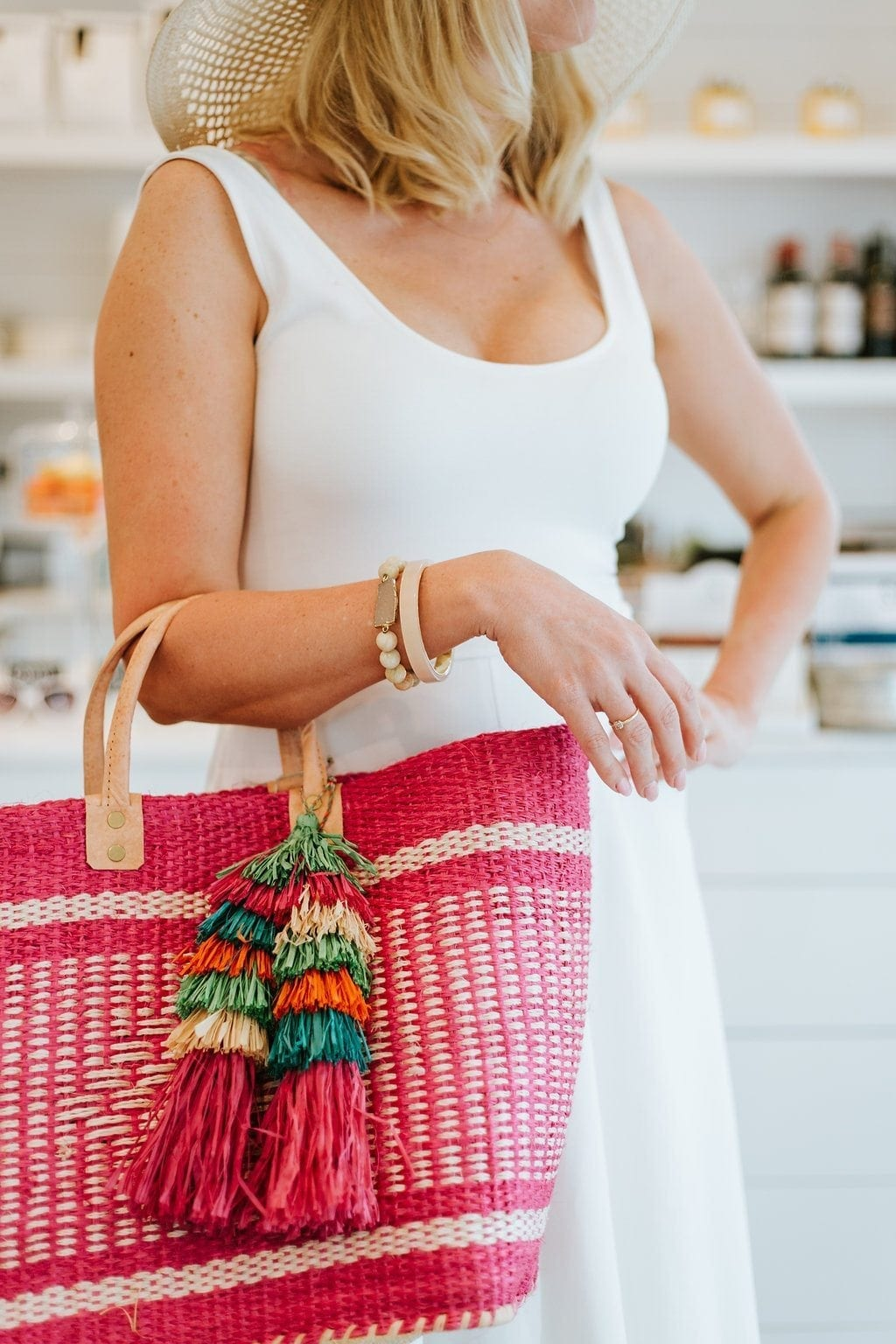 Pink beach bag adds a little something something to every beach outfit. Get this beach bag for vacation that has gorgeous leather handles and pink stripes with pink and multicolor tassels. A great beach essential!