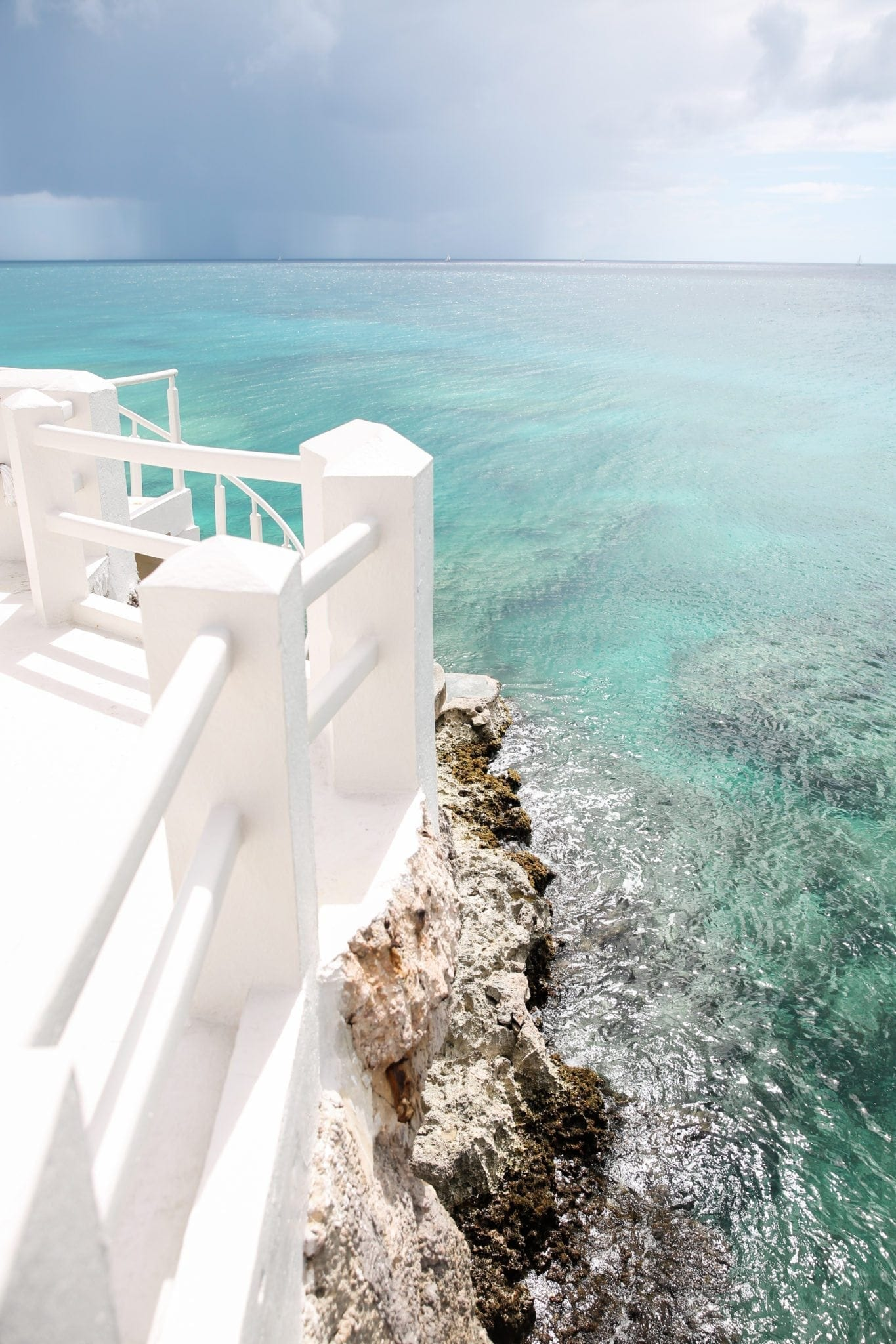 5 benefits to a travel agent. Anguilla Four Seasons resort view of ocean rocks from white bridge.