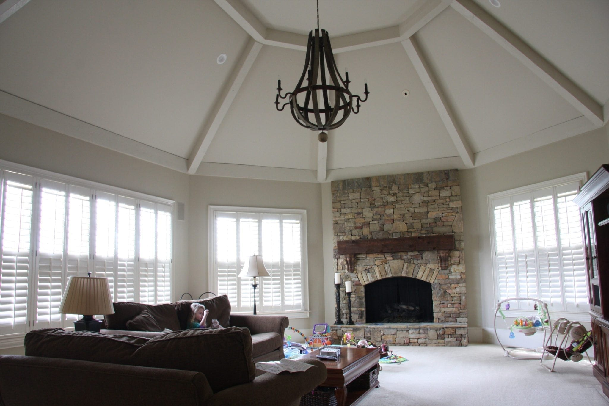 Room with painted ceiling beams in family room with stone fireplace.