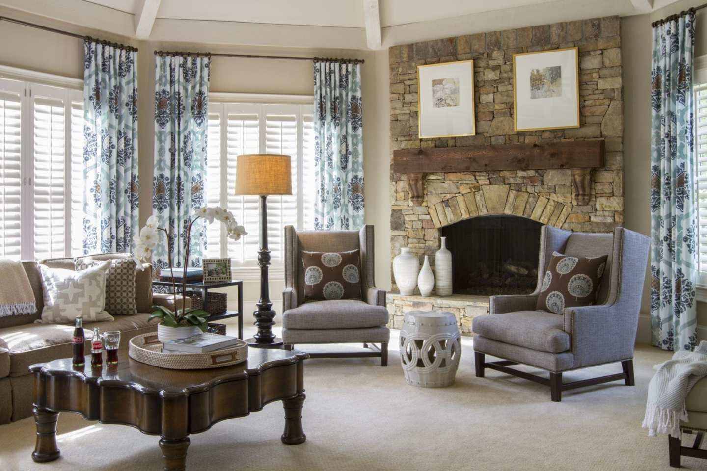 Traditional family room with stone and wood fireplace and blue drapery.