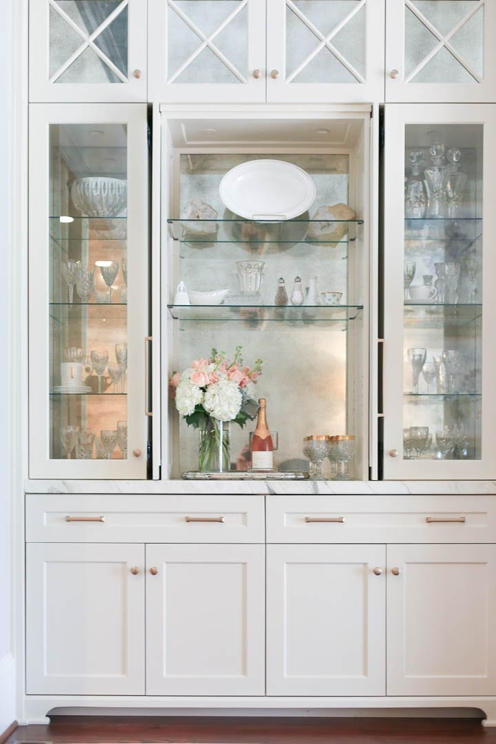 White built in with gold hardware for china display cabinet with peach roses and white hydrangea flower display.