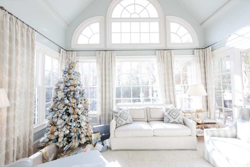 Light blue paint colors for your home. Sunroom filled with light. Large windows in blue and neutral decorated room.