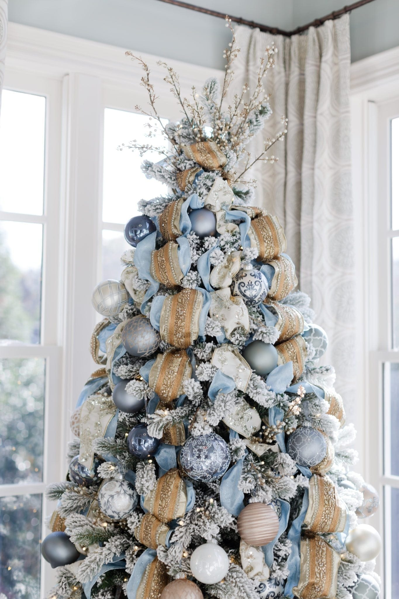 Gold embellished ribbon with light blue glitter ribbon on a flocked Christmas Tree.