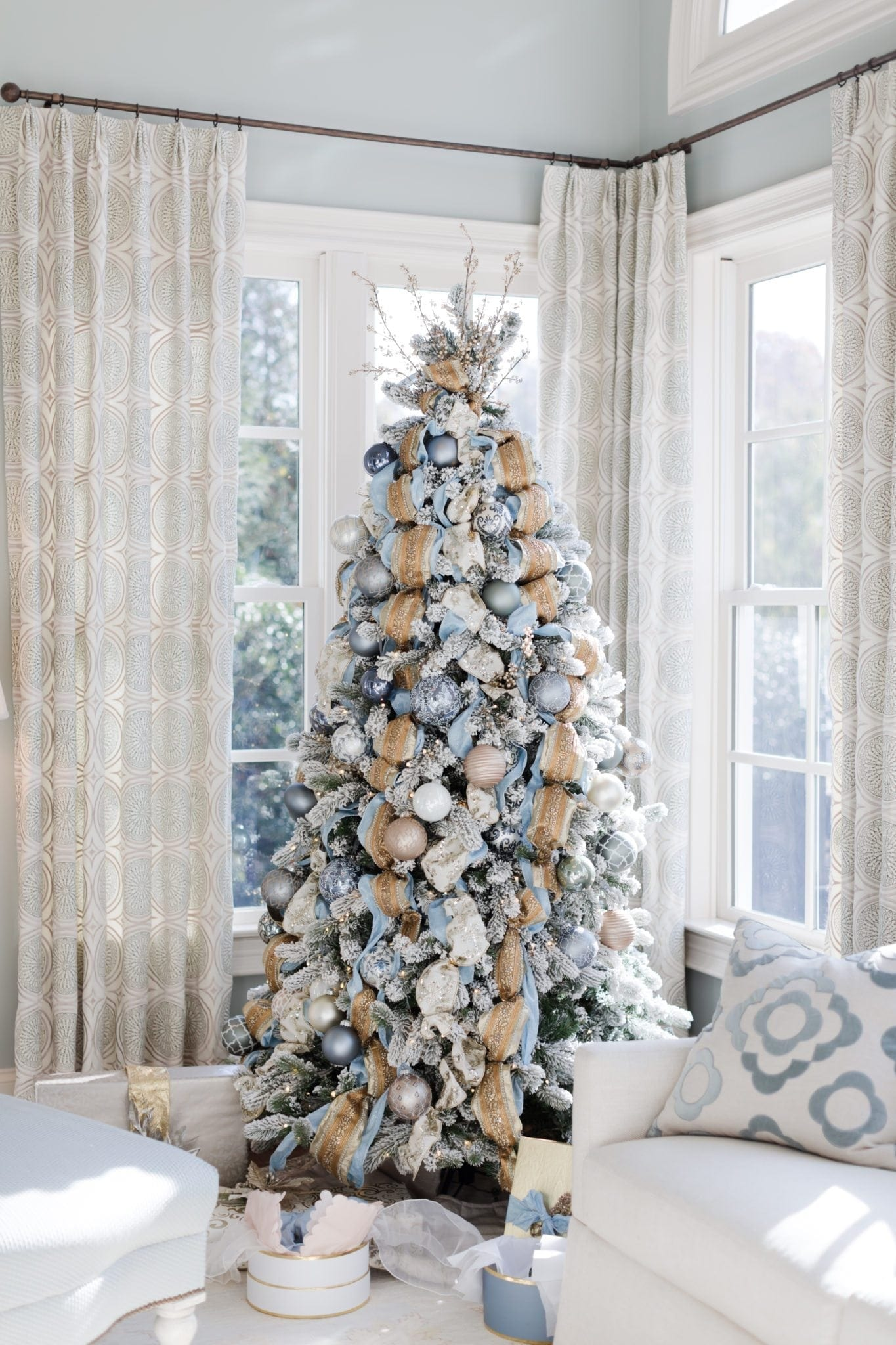 Gold ribbon and blue ribbon on blue and gold Christmas tree with gold and silver ornaments.