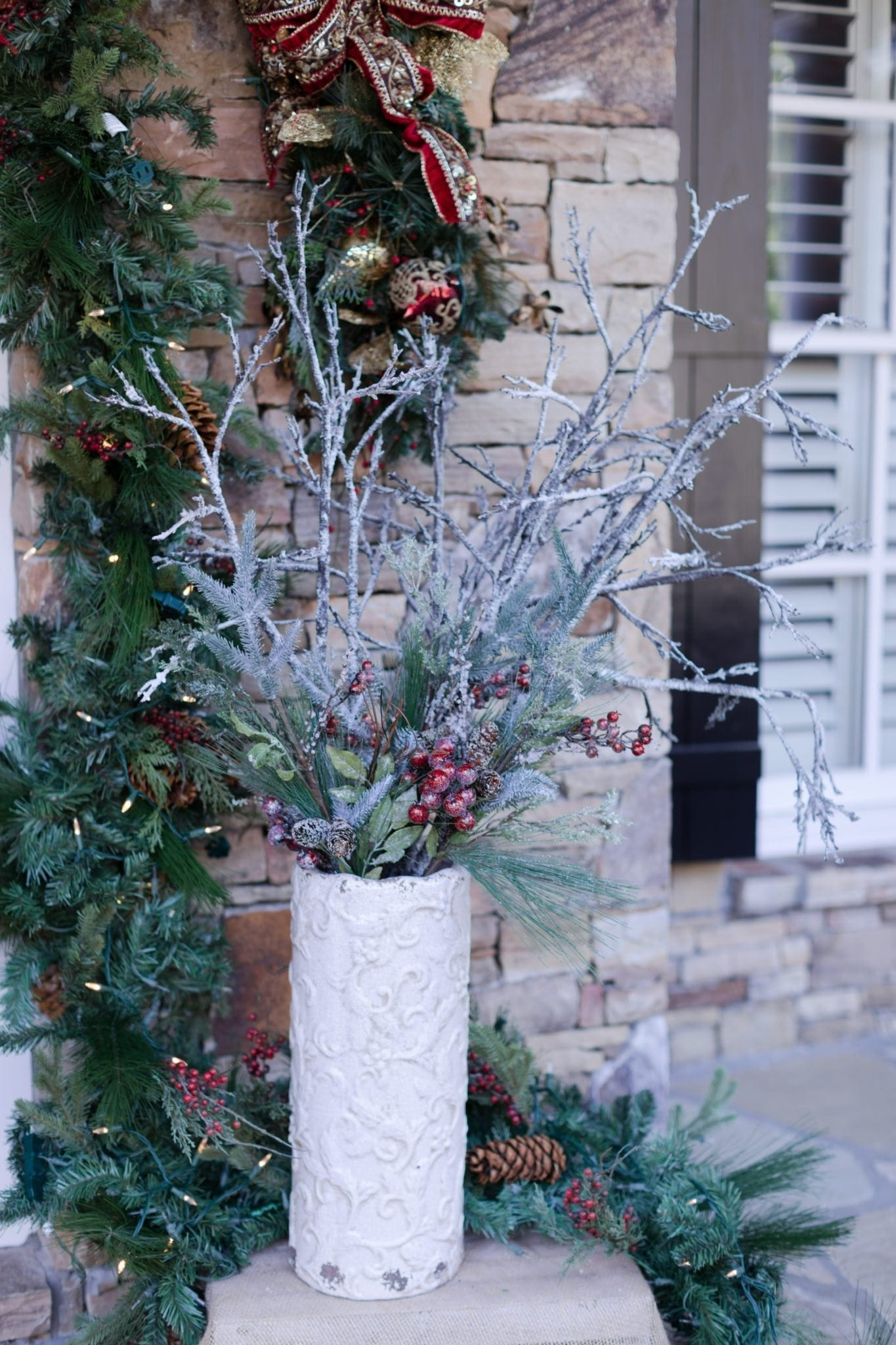 Frosted white branches mixed with holiday berries to set at front door for Christmas.