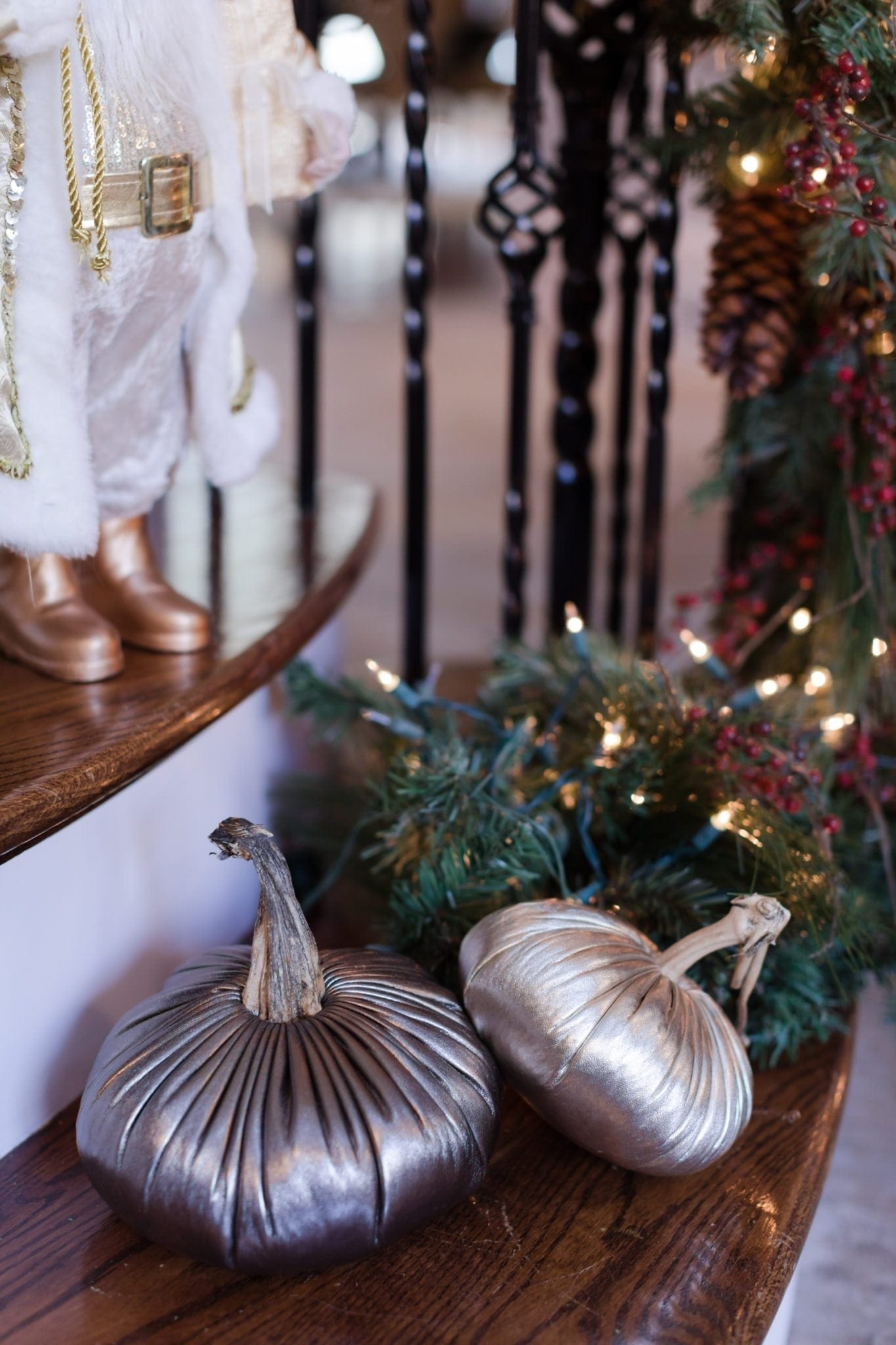 Gold leather pumpkins mixed with artificial garland at the base of a staircase.