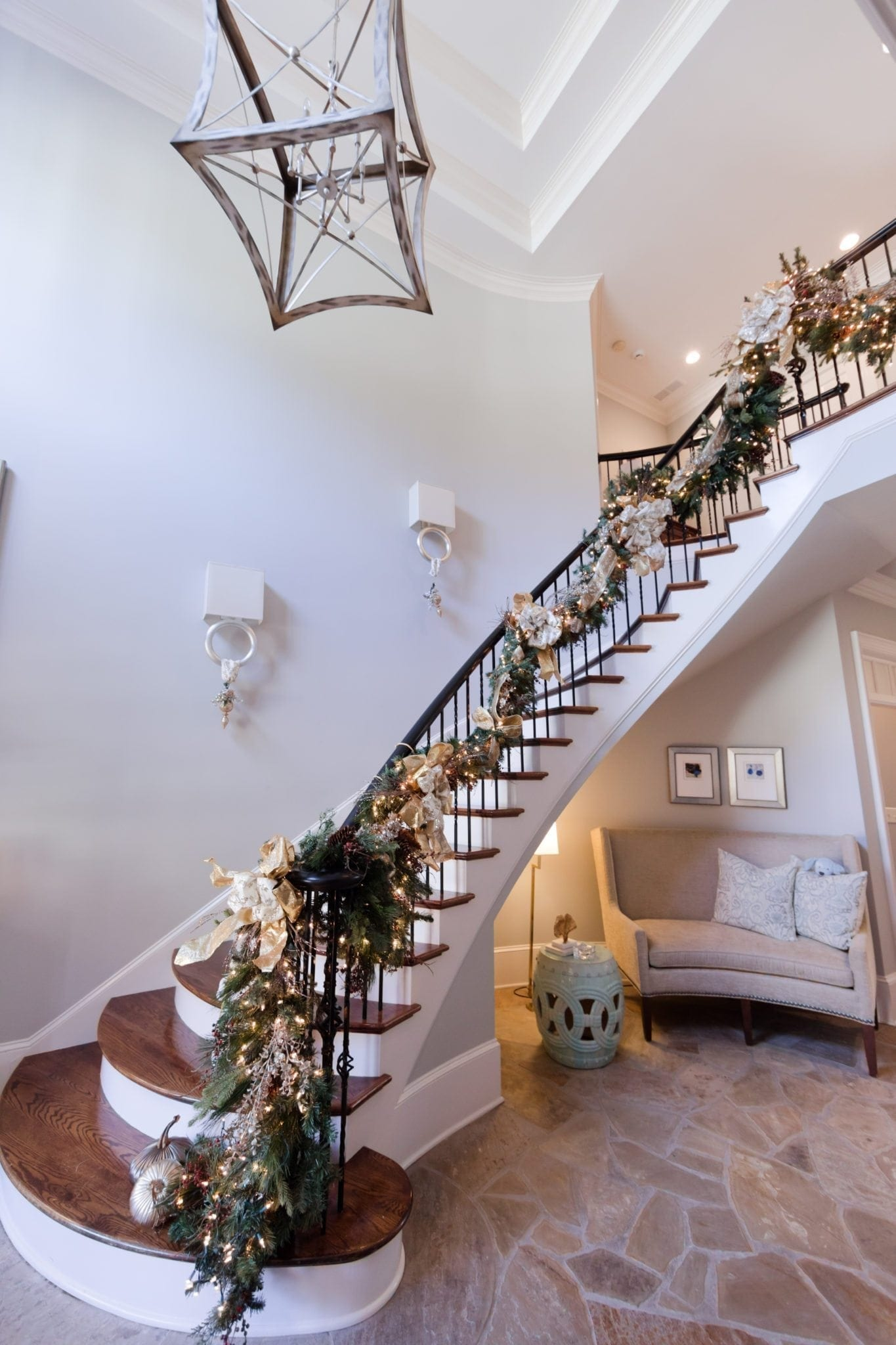Ideas for decorating a staircase for Christmas. Swagging garland on tall staircase in foyer.