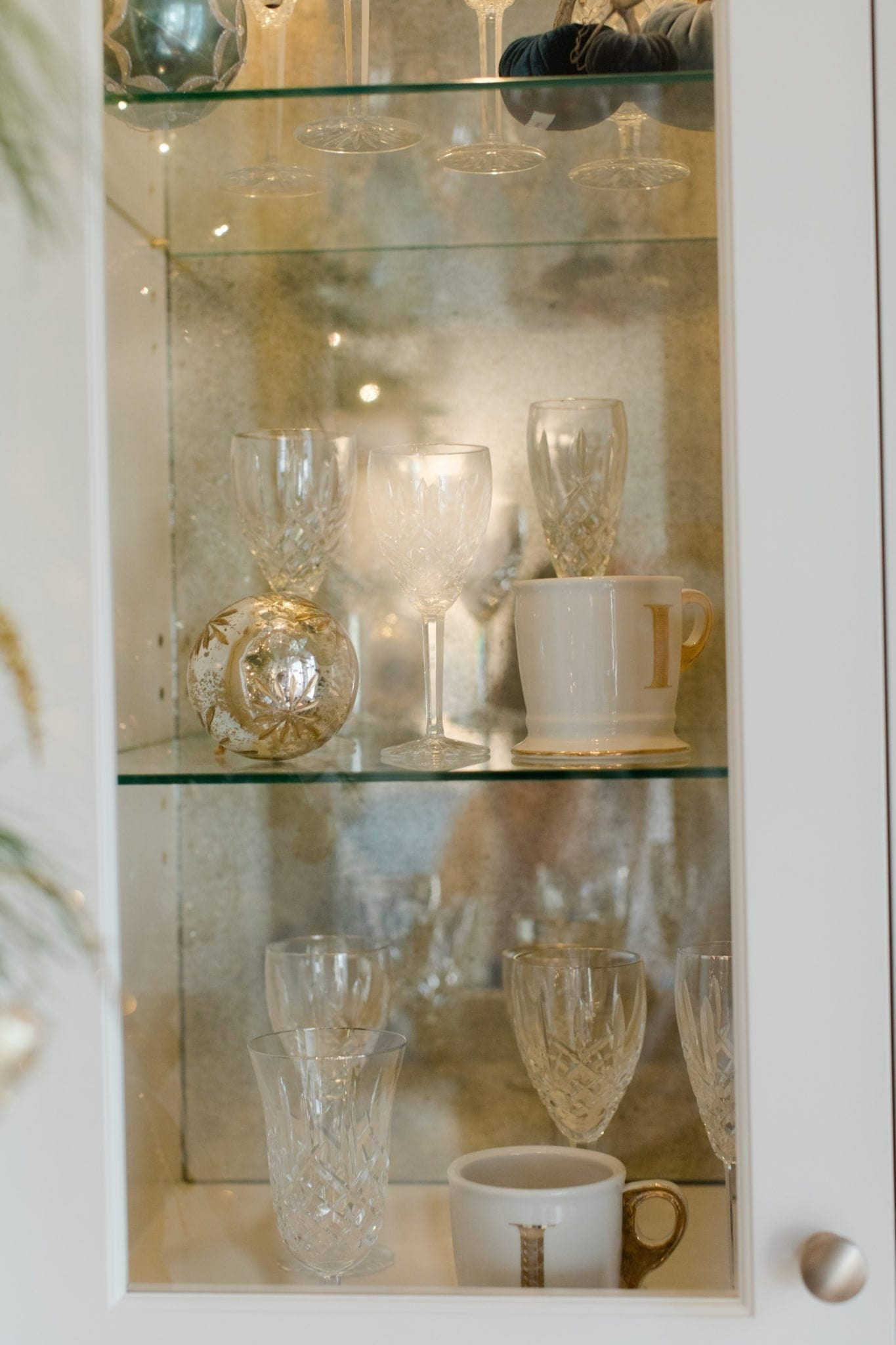 Ornaments inside a custom white china cabinet.