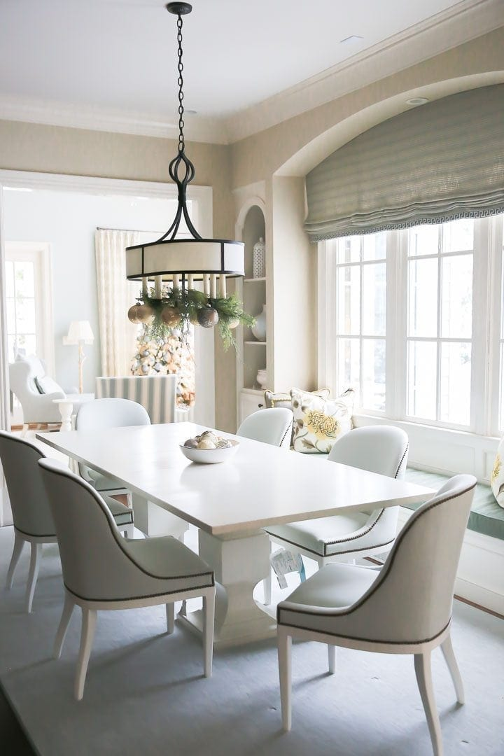 Garland in light fixture in kitchen for Christmas. Light blue upholstered chair and white pedestal kitchen table.