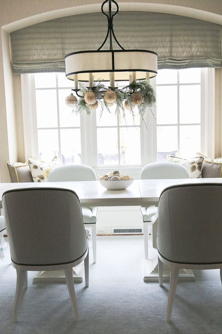 White kitchen table with light blue chairs with railheads.