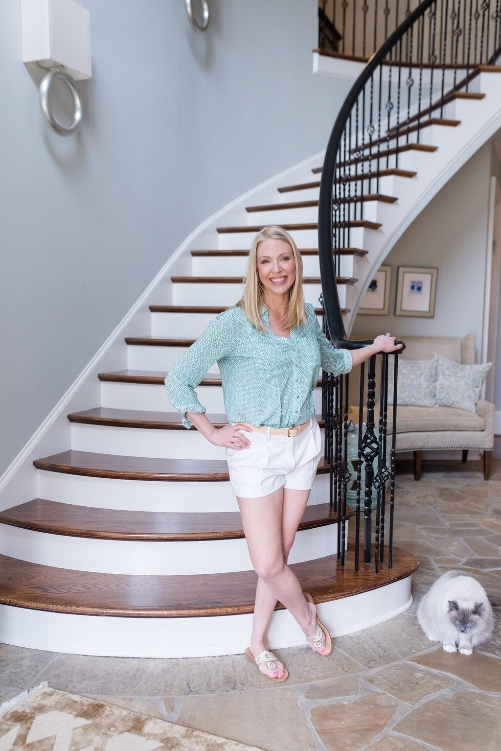 Atlanta home blogger Kelly Page in home entranceway with stone flooring and Stark Carpet.
