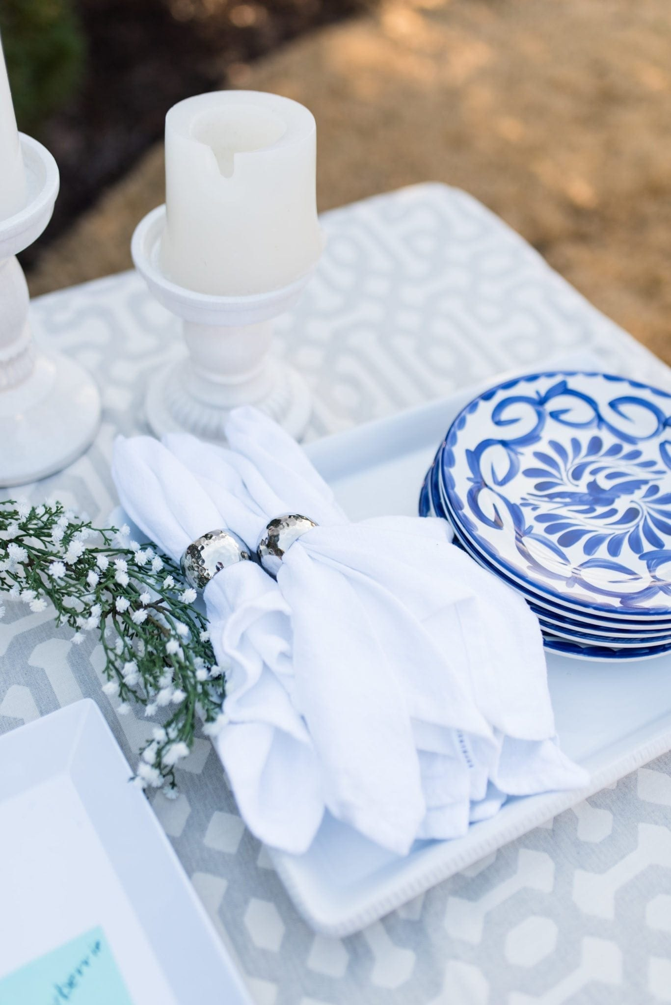 Easy and simple party set up. All white and blue table setting with pretty blue and white plates, white linens and babies breath.