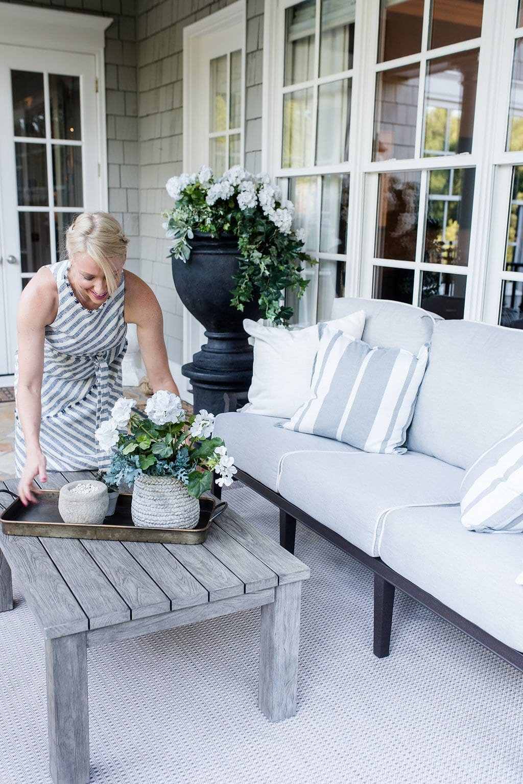 Atlanta Homes magazine. Setting a teak coffee table with tray and outdoor accessories.