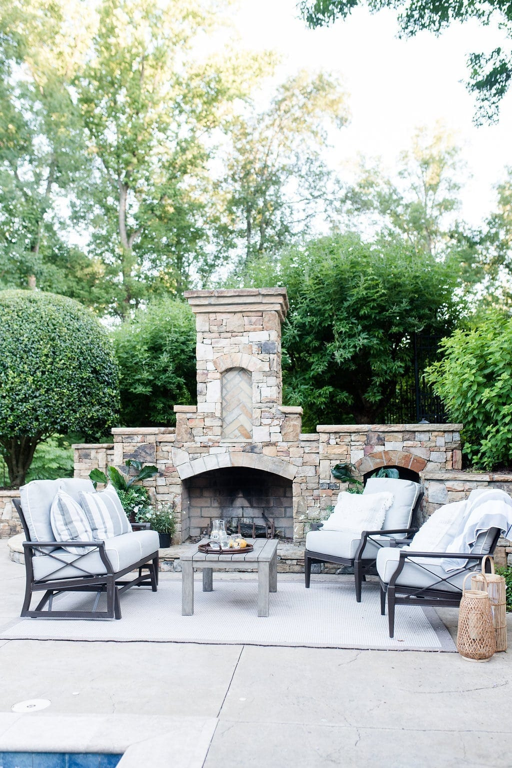Outdoor fireplace furniture. Rocker glider chairs and love seat by the fireplace.