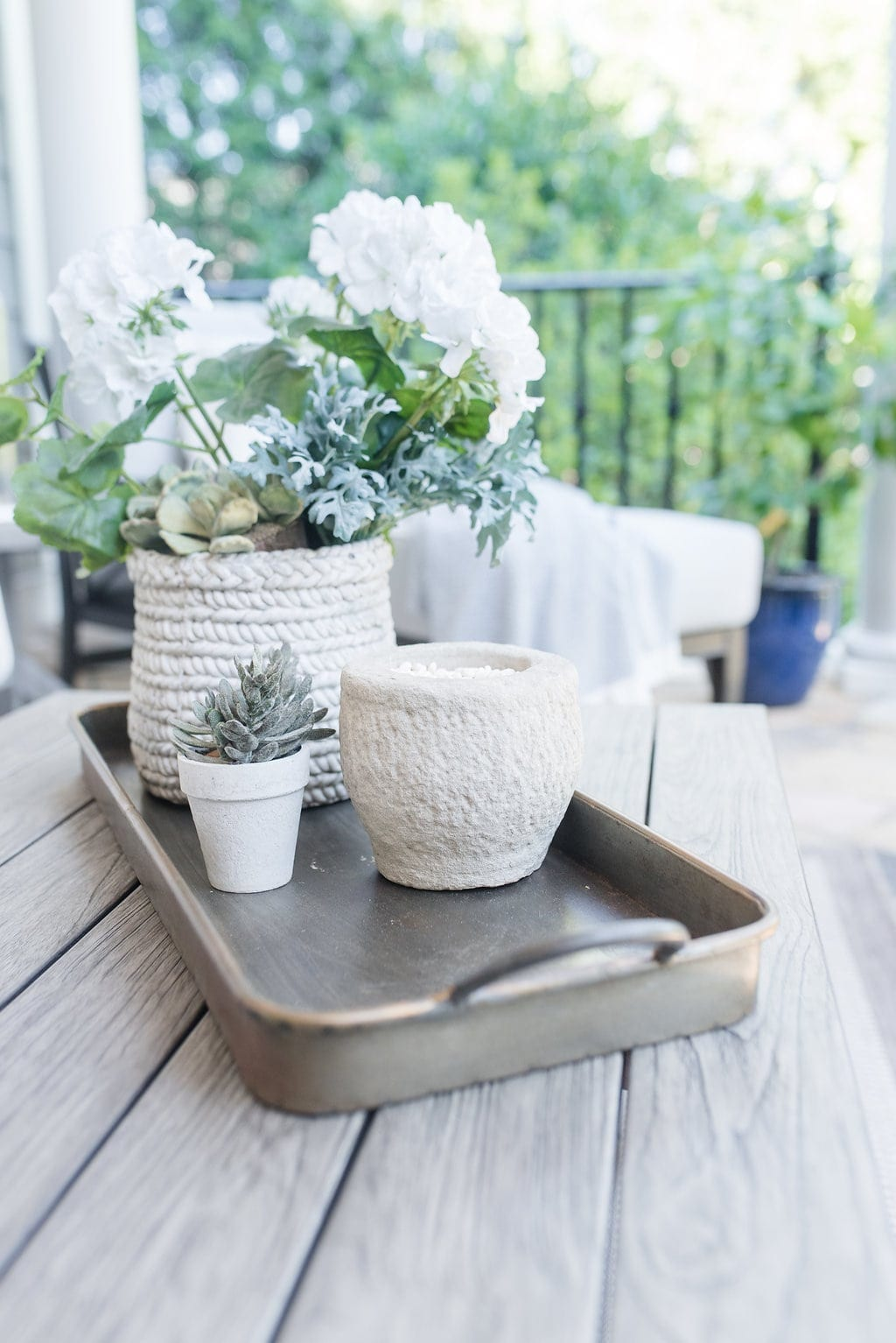 Accessorizing outdoor spaces. Gray aluminum tray with gold, faux succulents and faux flowers.
