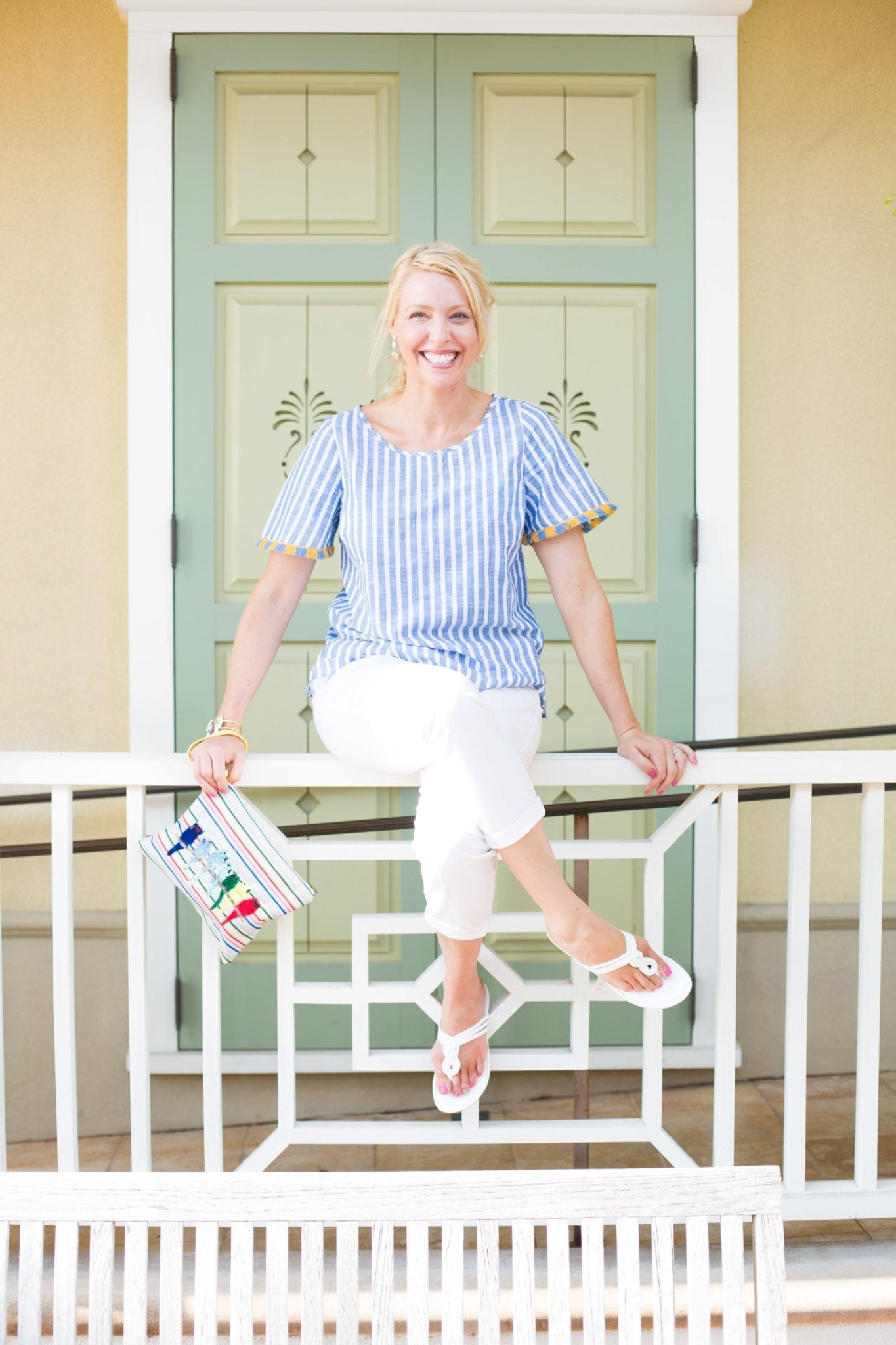 Blue and white stripe shirt with fringe on sleeve. Yellow and blue fringe and white sandals with colorful clutch.