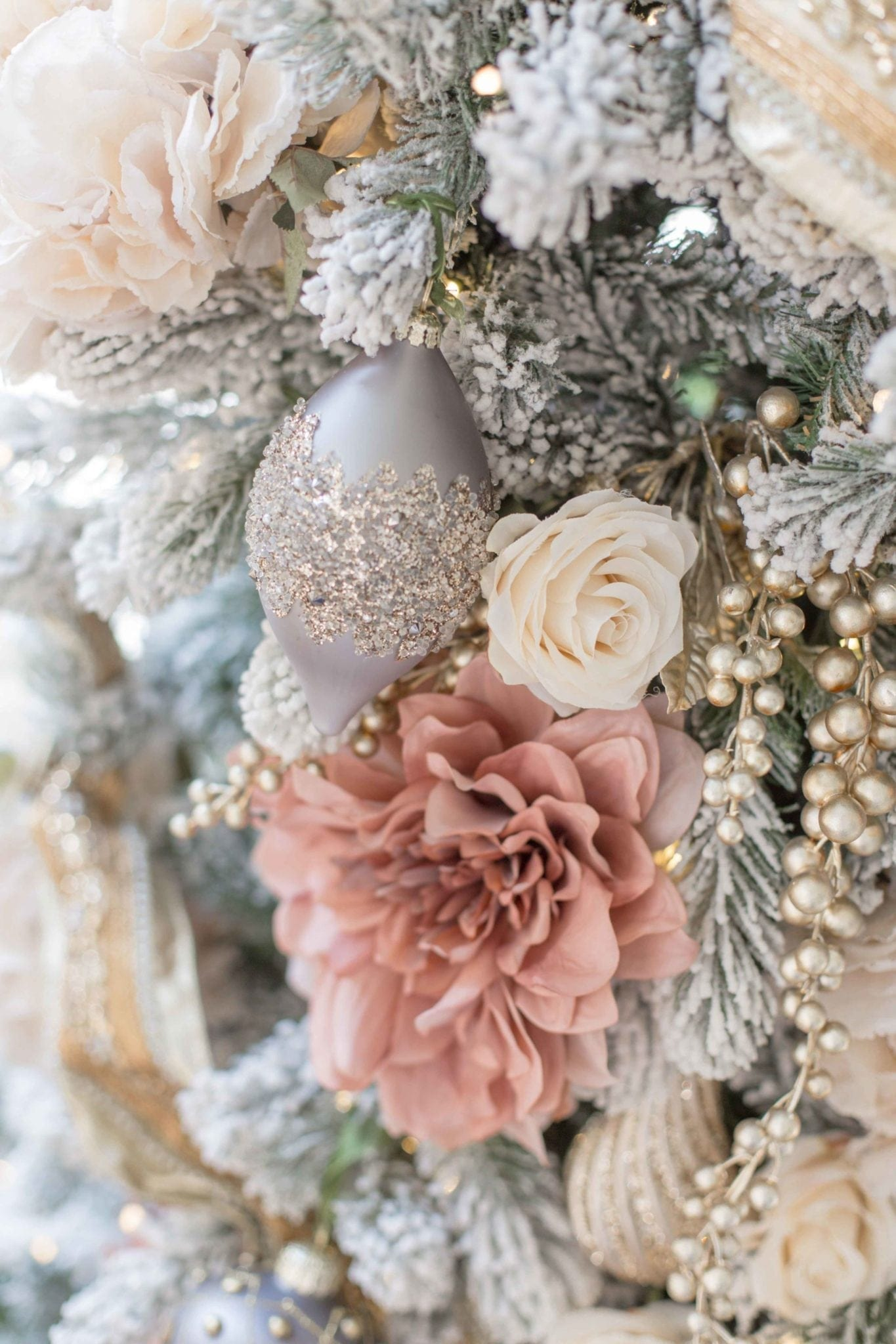 Artificial roses and gray ornaments add a pretty gray and pink design to this King of Christmas artificial tree. Tips to decorate a gray, pink, ivory and gold Christmas tree!
