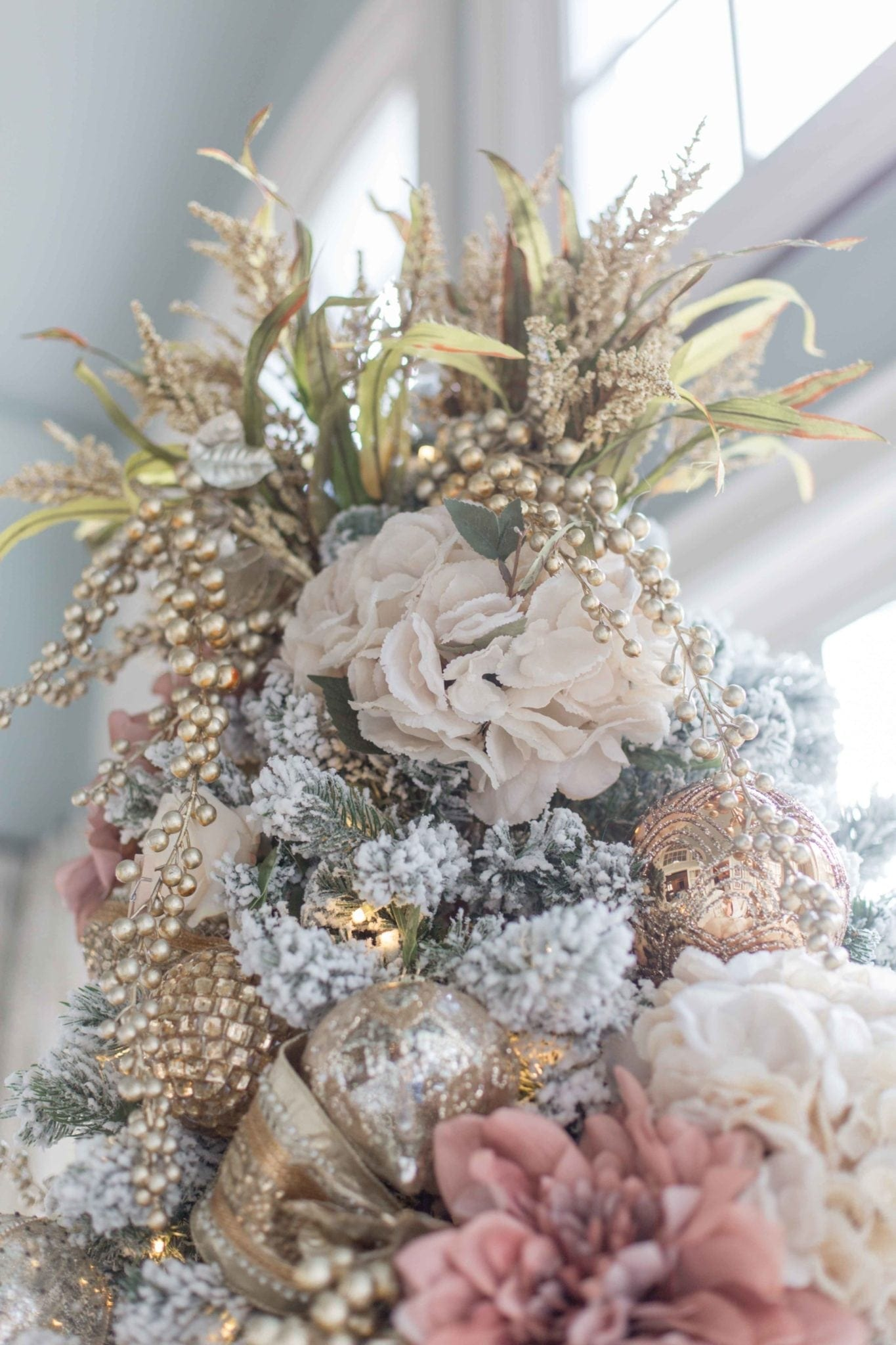 Unique way to decorate the top of a tree! Use gold faux flowers and gold picks to make the tree topper pop!