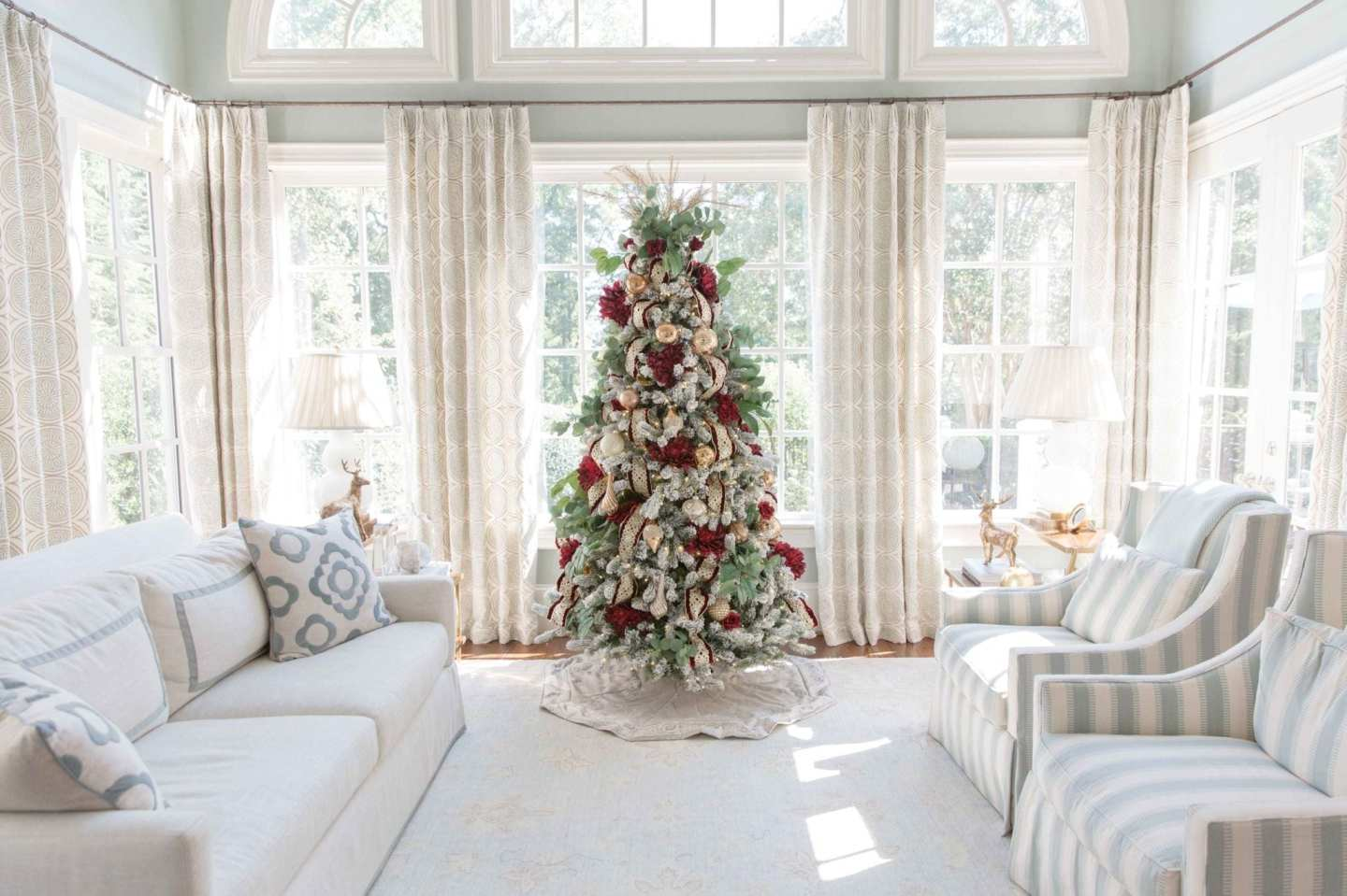 Red and Gold Christmas Tree Decorations. Decorate your Christmas tree in red and green. Artificial flowers bring this flocked tree to life with Christmas spirit in all things red and green and snowy white! Inspiration for how to decorate one tree in two very different styles!