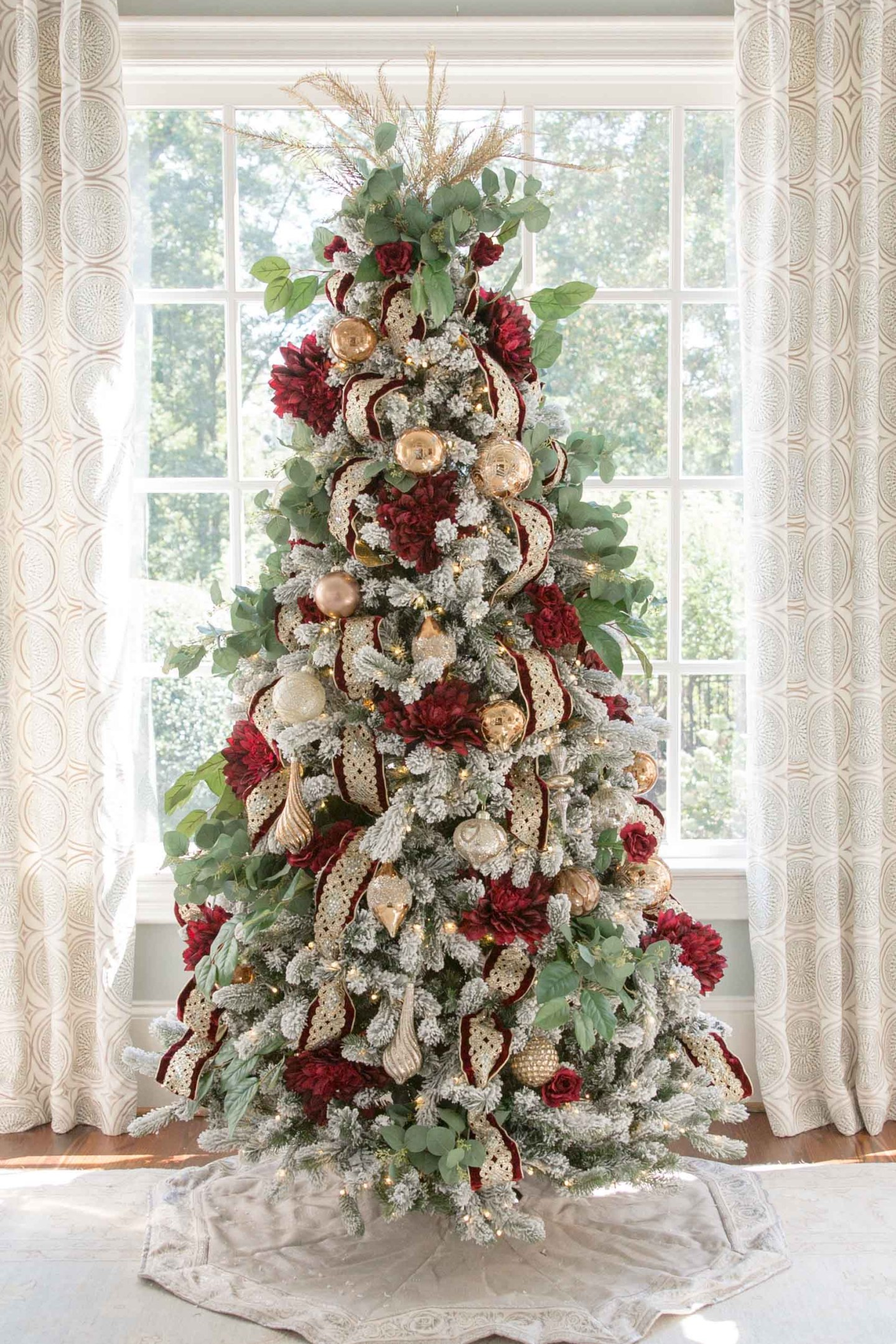 Red and Gold Christmas Tree. Intricate and ornate gold wired ribbon, dark red dahlias and deep red roses decorate this flocked tree in traditional colors. See two ways to decorate a flocked Christmas tree. More how to design a traditional tree posts coming soon!