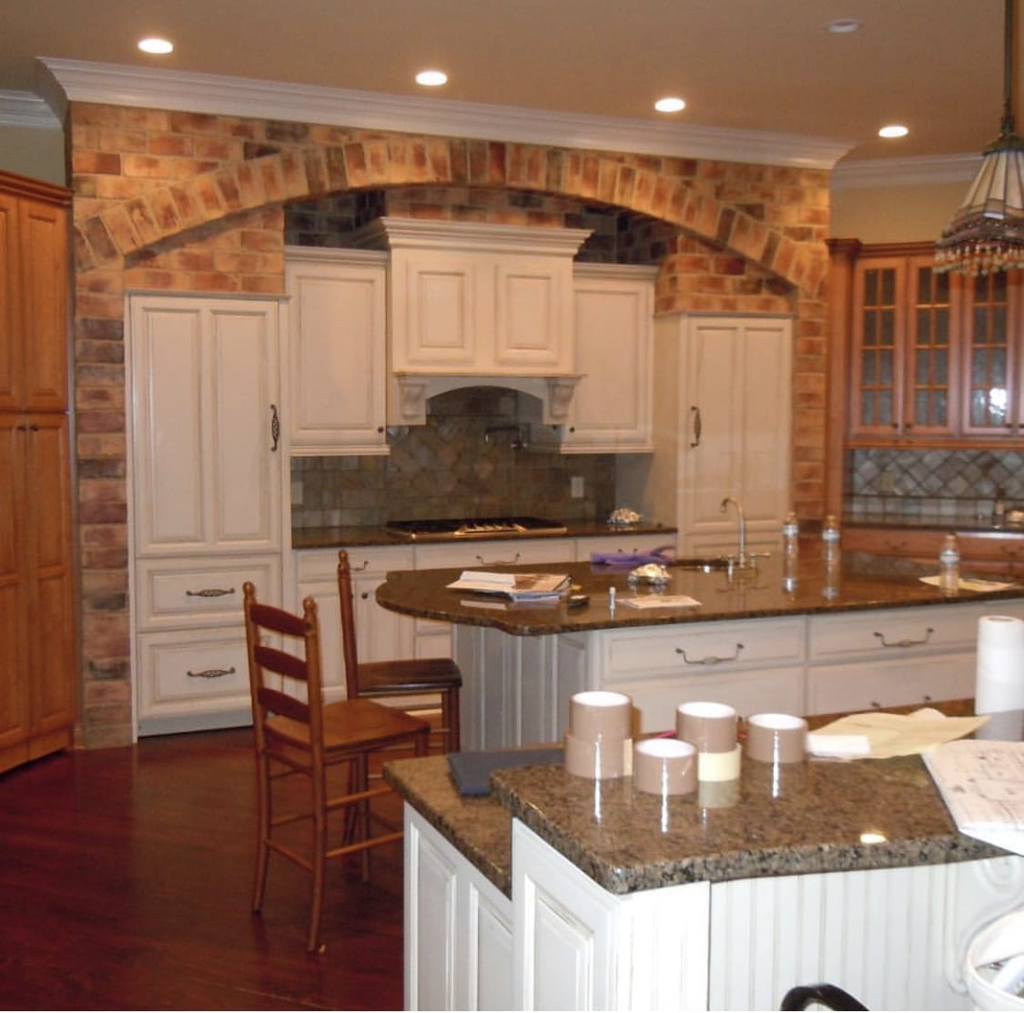 Kitchen with faux brick and white cabinetry,