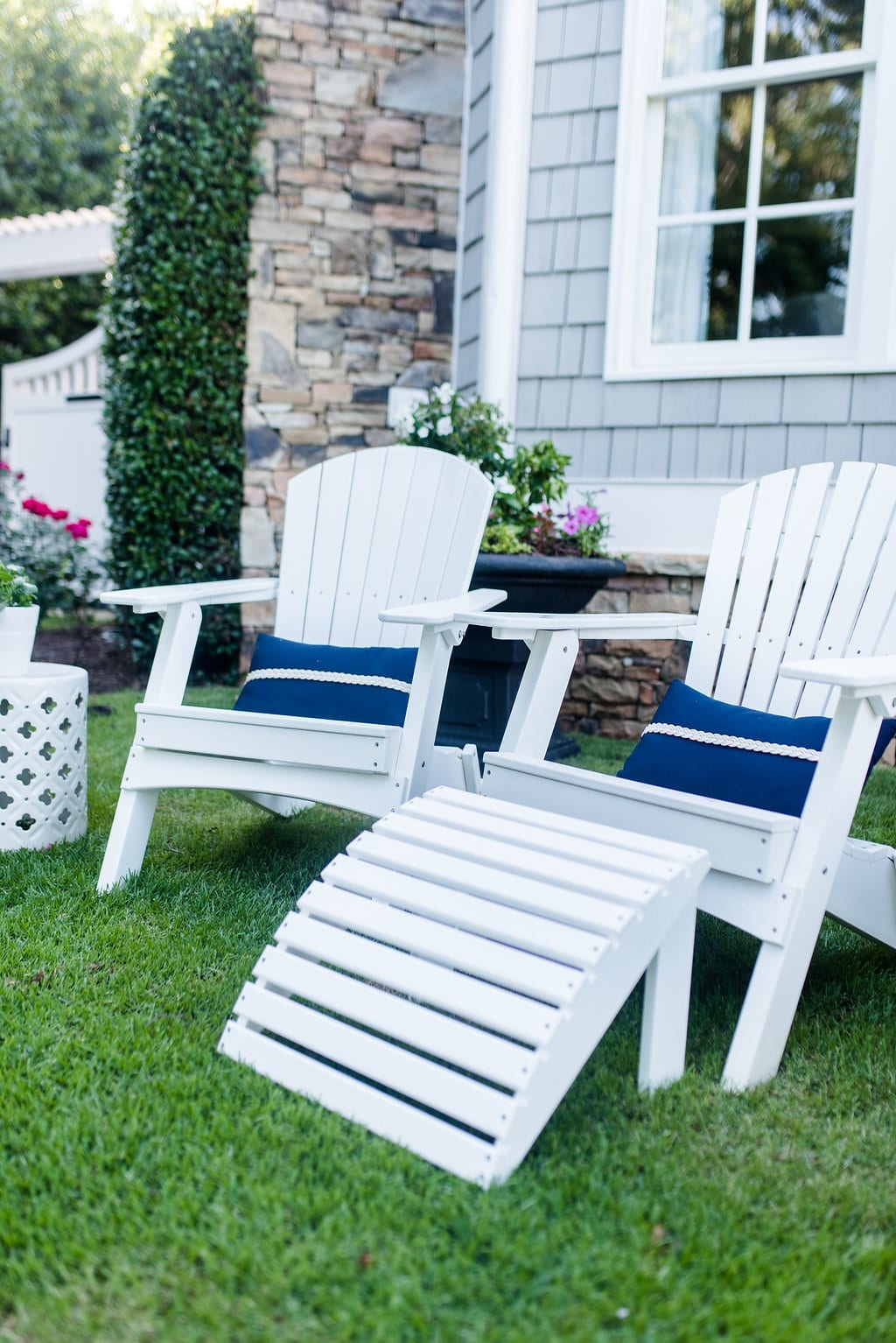 White Adirondack Chairs on Sale with navy blue nautical outdoor pillows.