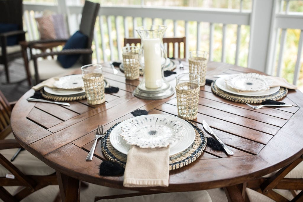 Outdoor table setting ideas. Make a rustic wood table pop with glamorous plates from Anthropologie home and rattan chargers.