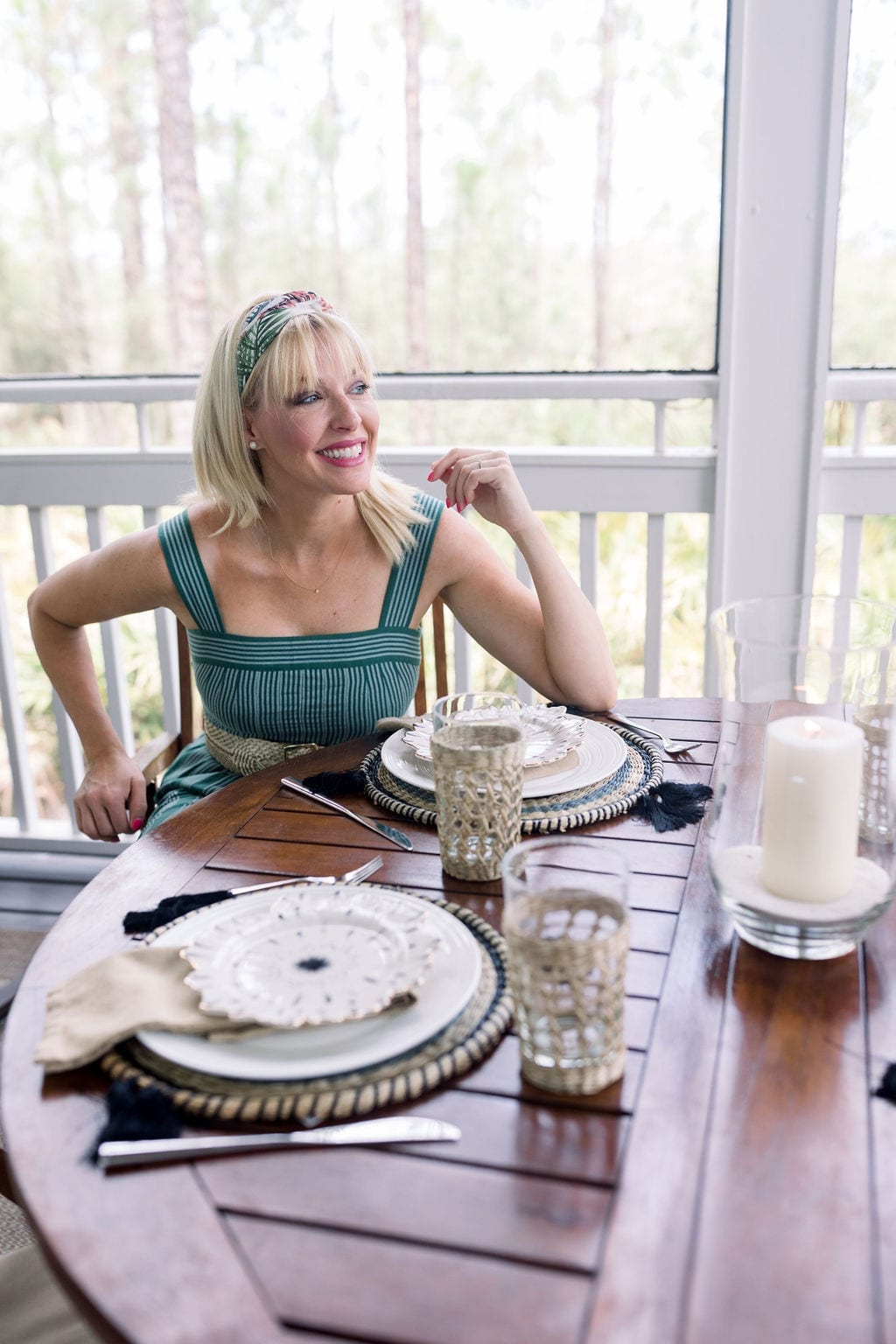 Table settings with round placemats for outdoor coastal glam table setting with accents of wicker, black and gold.