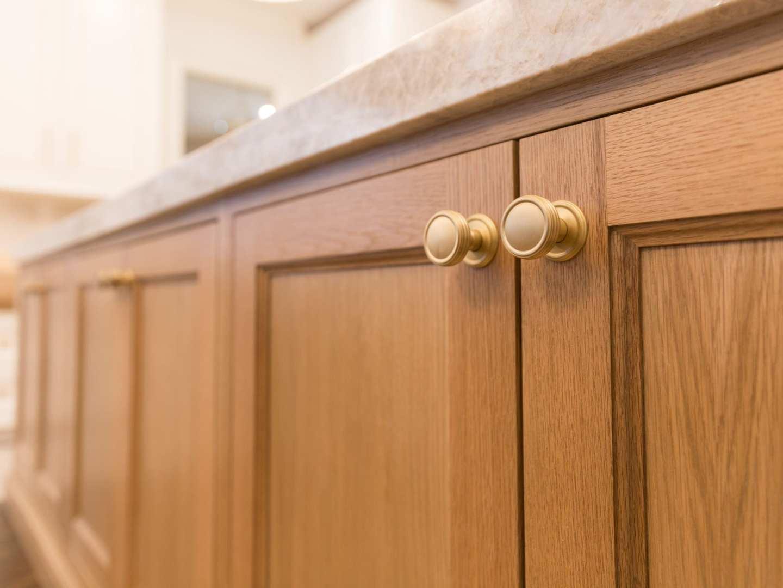 Oak Kitchen Cabinets with Taj Mahal quartz and VESTA gold hardware.