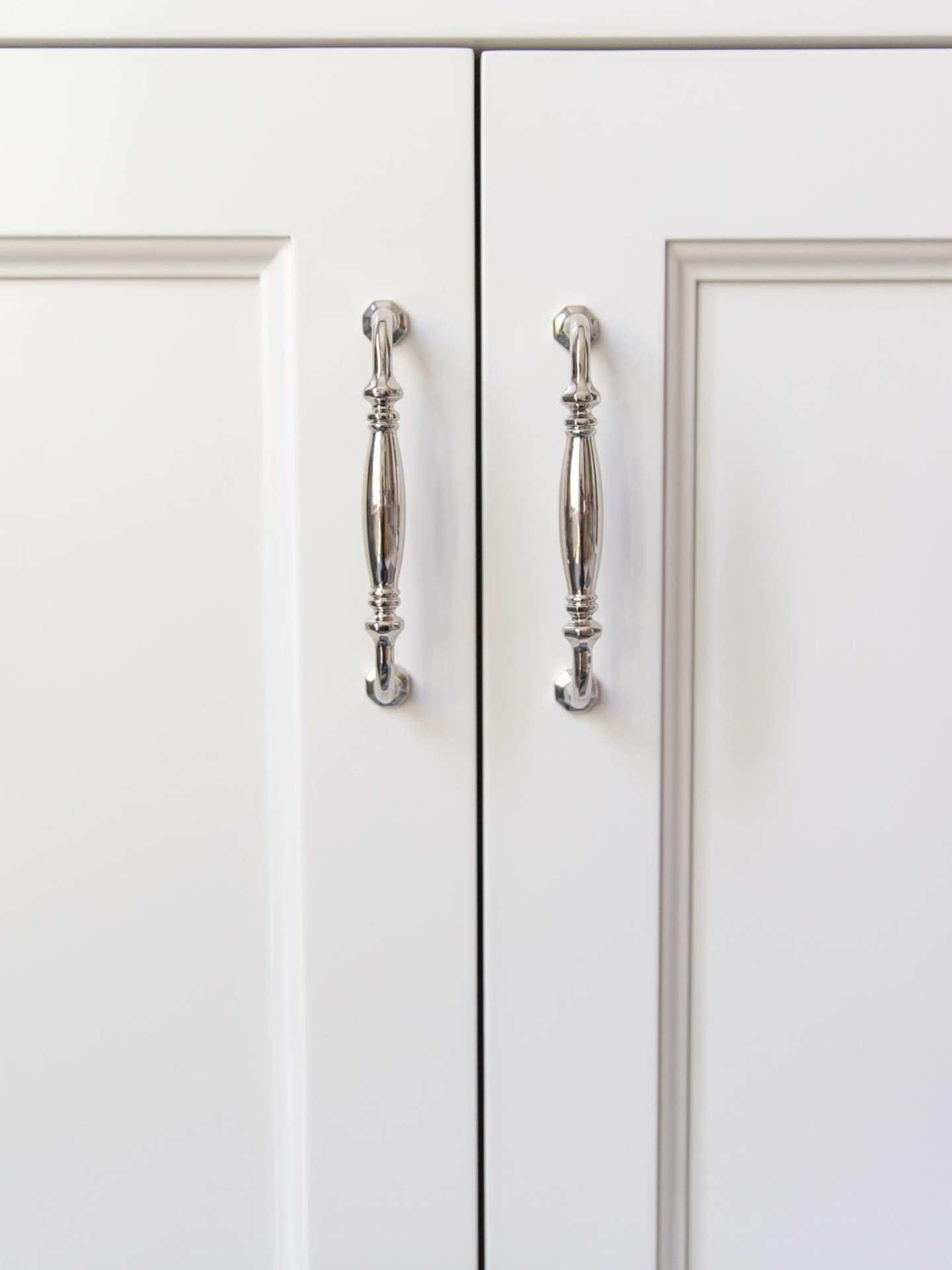 Polished Nickel Hardware on white bathroom cabinets.