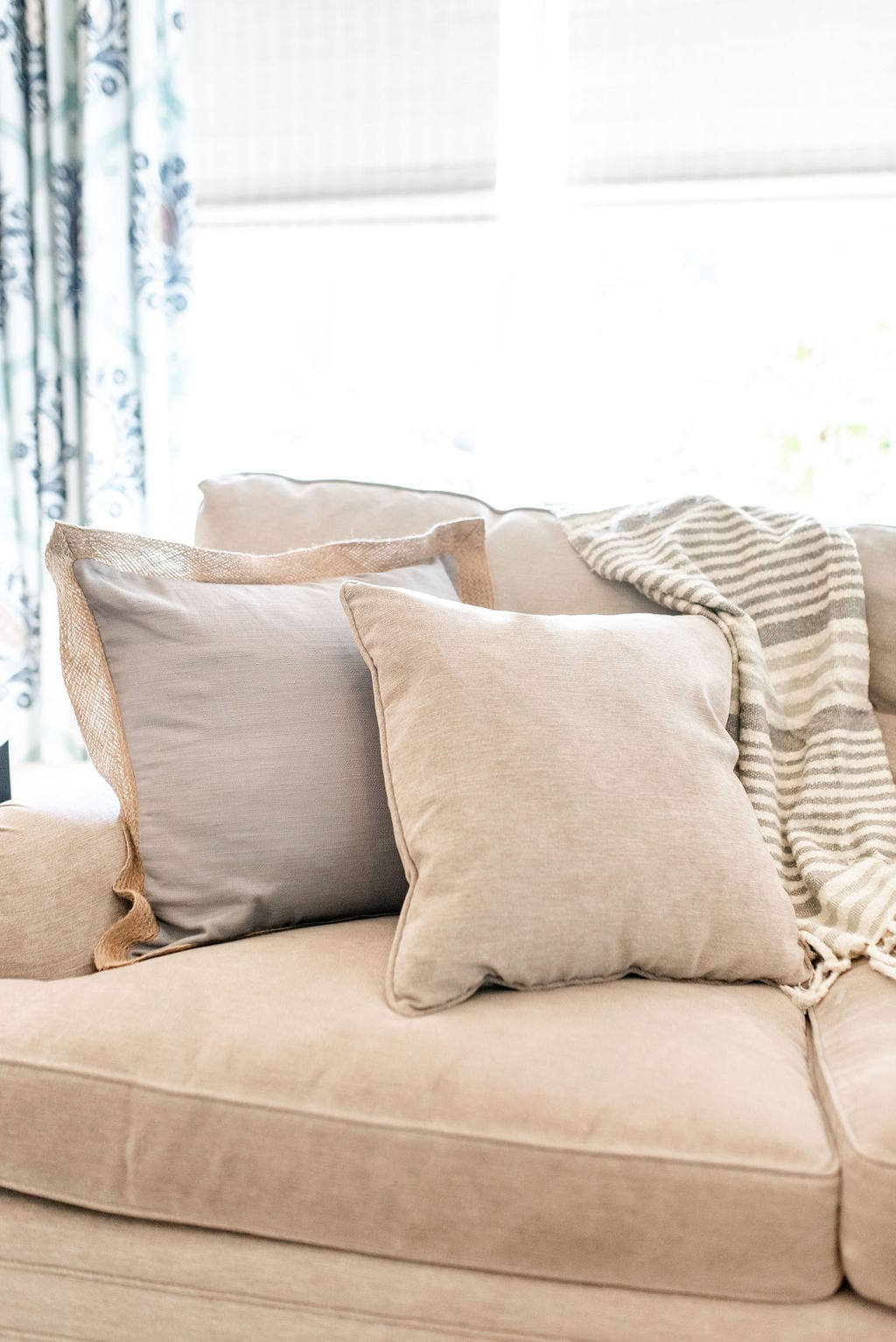 Chenille Taupe Couch with burlap throw pillow. Theordore Alexander couch with taupe stripe throw blanket from Wayfair.