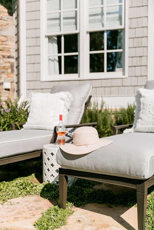 Comfy oversized chaise lounge chairs. Cedar house exterior Cape Cod style with gray outdoor furniture and white garden stool.
