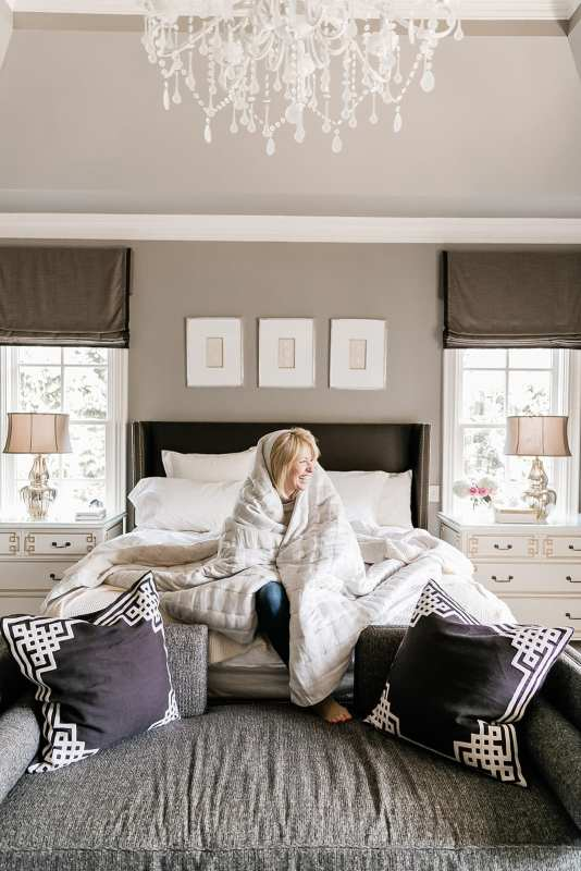 Atlanta blogger Kelly Page, BlueGrayGal, in master bedroom decorated with white chandelier, intaglio prints, gray Benjamin Moore paint, blue bench and ivory Annie Selke bedding.