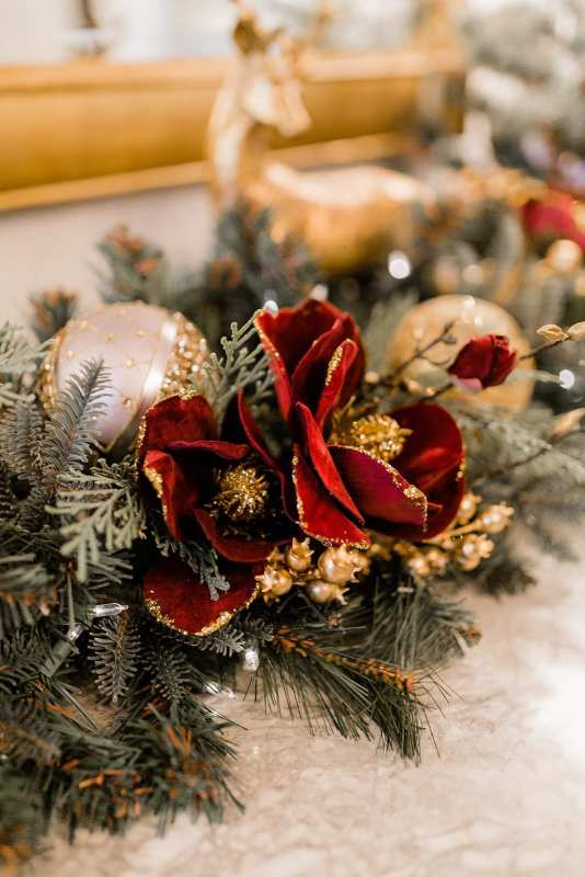 Red and gold magnolia garland. Gold tree picks and light gray ornaments mixed with gold glitter.