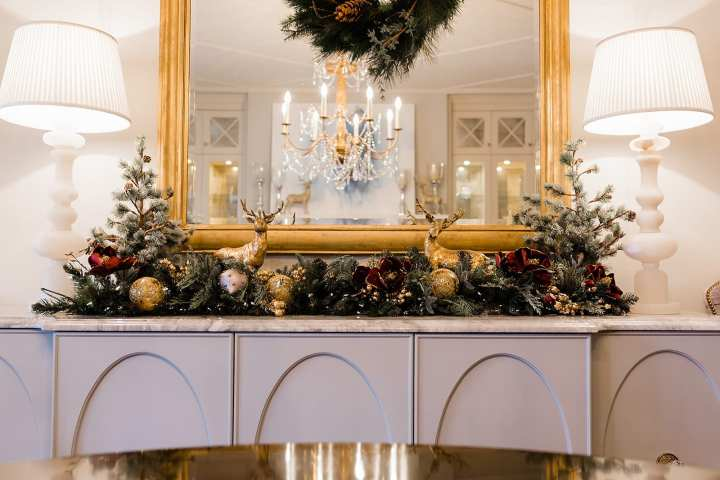Magnolia garland with lights. How to create a glamorous dining room setting for Christmas with gold reindeer and white table lamps.