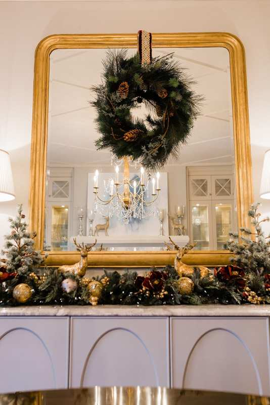 Grand dining room with gold chandelier and christmas wreath on mirror. Frontgate garland and holiday decor in dining room on tabletop with gold ornaments and holiday garland.