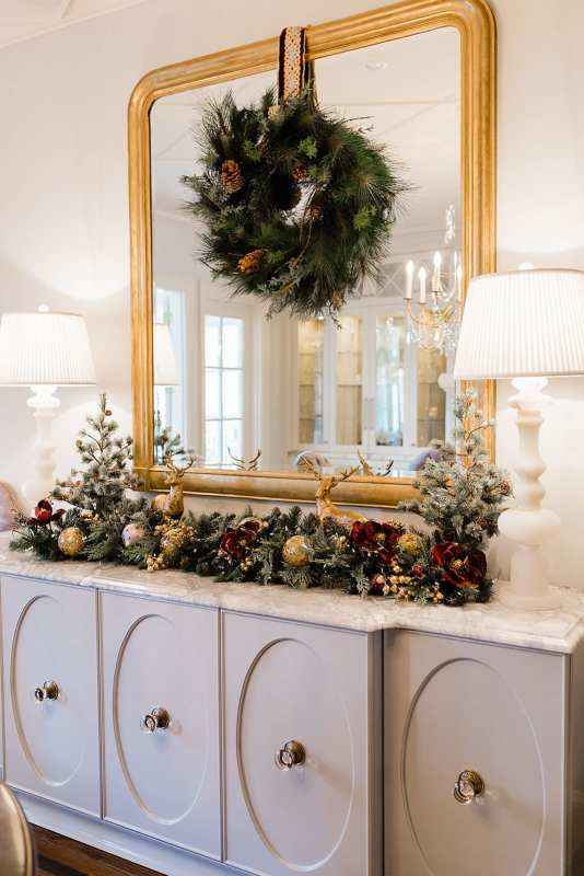 Christmas dining decor ideas. Gold ornate mirror with wreath hanging with Frontgate ribbon and white marble lamps.