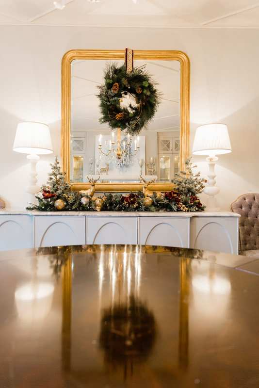 Glamorous dining room christmas table with gold ornate mirror in dining room with holiday wreath hanging from mirror. White Currey and Company marble lamps and Frontgate holiday decor in Atlanta blogger BlueGrayGals home.