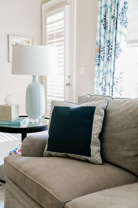 Light blue lamp in family room. Blue drapes, navy blue velvet pillow and taupe couch.