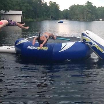 girls jumping off water trampoline
