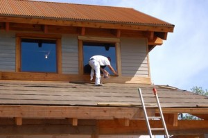 One worker puts stain on the trim of a second story window.