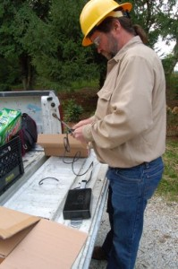 "A crewman with Elliot readies an IBEC ""black box"" for installation to the pole."