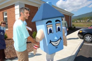 Bill Hess of Afton, shakes the hand of Homer the mascot at Community Day in Nellysford, Virginia