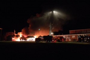 A larger ladder truck stands by as the old classroom burns to the ground.