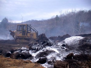 A bulldozer from the VA Department of Forestry pushes burned debris at Wednesday's fire.