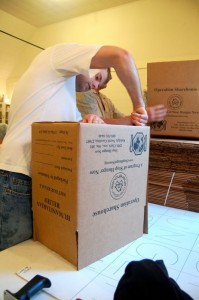 Church volunteers tape up boxes used for shipping in Operation Sharehouse.